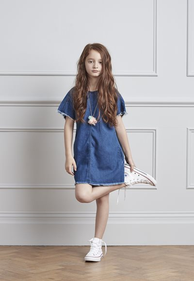 Bubble London, Young girl standing in a denim dress holding her foot up, childrenswear, new childrenswear trends, fashion for children, kid's fashion, fashion for kids, trends for kids fashion, fashionable kids clothes, clothes for children, childrenswear stores, clothes for kids, trendy clothes for kids,