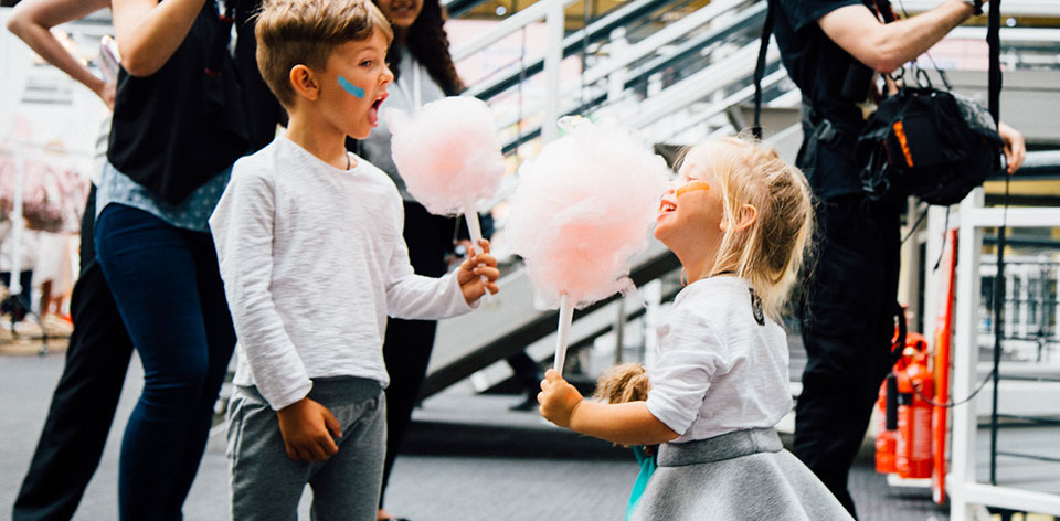 Young boy and girl eating candy floss and laughing, Bubble London, kids show, kids fashion, fun for children, fun event for kid's, girl's dresses, boy's clothes, busy trade show, happy children, excited children, exciting children's event, fashionable children, clothes for children, gifts for children,