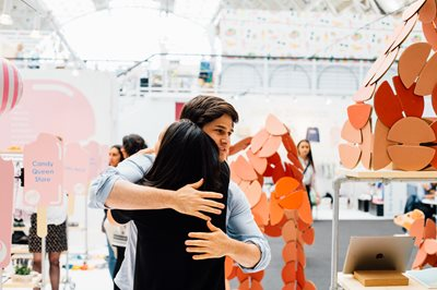 Young man hugging a lady with her back to the camera in front of exhibitor stands, children's toy, toys for children, BDC, Business Design Centre, fun children's toys, children's shops, tradeshow for childrenswear and toys, kid's toys.
