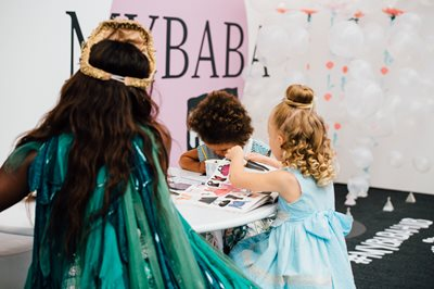 Bubble London, three children on a table playing with toy books and colouring in, children having fun, fun children's event, fun for children, kid's toys, kids being creative, safe fun activities for children, fun toys for children, Childrenswear tradeshow,