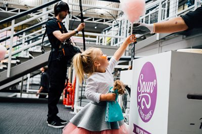 Bubble London, Young girl reaching up over a counter to grab candy floss from someone handing it to her, childrens food, children's event, fun event for kids, kids clothing, candy floss, children havign fun, childrenswear event, childenswear tradeshow,