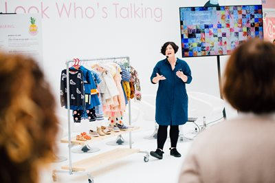 Bubble London, Woman speak addressing an audience  next to a rack of children's clothing, childrens clothing, clothes for children, professional speakers, childrenswear industry, clothes tradeshow, tradeshow for clothes, childrenswear clothing, buy childrenswear, pitching childrenswear,