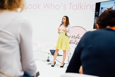 Bubble London, Female speaker with a microphone addressing audience with a presentation behind her, childrenswear trends, trends in children's clothing, clothes for children, ki'ds clothing, ki'ds clothing trends, kid's fashion shops, shops for children's clothing